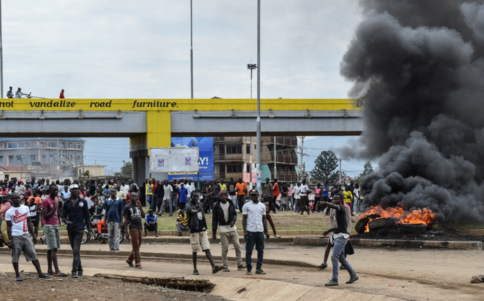 FILE: Supporters of opposition coalition the National Super Alliance stand next to tyres on fire in Kisumu, western Kenya, on 13 October 2017 during a protest against the re-run of the presidential election. Picture: AFP