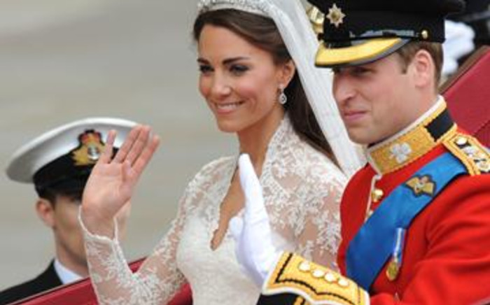 Britain's Prince William and his wife Kate, Duchess of Cambridge, wave as they travel to Buckingham Palace in a carriage. Picture: AFP