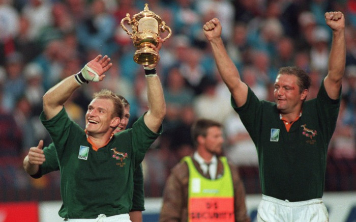 South African captain Francois Pienaar (left) brandishes the Rugby World Cup and salutes the crowd with teammate Hannes Strydom (right) after the 1995 Rugby World Cup final match between South Africa and New Zealand at Ellis Park Stadium in Johannesburg on 24 June 1995. Picture: AFP.