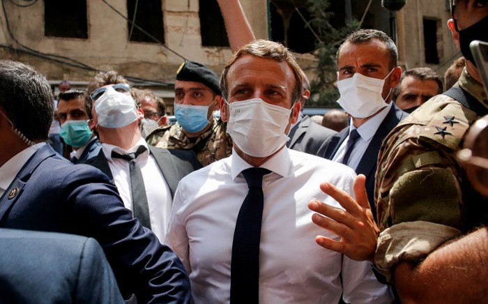French President Emmanuel Macron (C) visits a devastated street of Beirut, Lebanon, on 6 August 2020 two days after a massive explosion devastated the Lebanese capital in a disaster that has sparked grief and fury. Picture: AFP