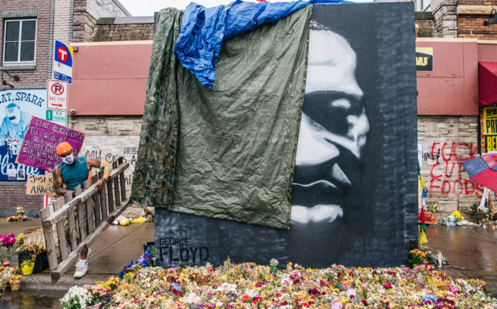 Men cover a painting of George Floyd at his memorial site on June 9, 2020 in Minneapolis, Minnesota. Residents of the community, and people around the world, have come together in calling for an end to police brutality after the death of George Floyd, who was killed while in Minneapolis police custody on May 25th. Picture: Brandon Bell/Getty Images/AFP