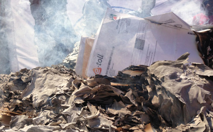 Gauteng anti-e-toll protesters have set their unpaid e-toll bills alight in front of Sanral's offices. Picture: Reinart Toerien/EWN.