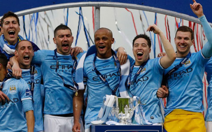 Manchester City players celebrate with the League Cup during the presentation after Manchester City won the League Cup final against Sunderland at Wembley Stadium in London on 2 March 2014. Picture: AFP.