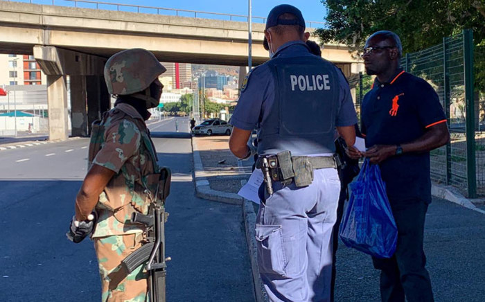 FILE: An SANDF soldier and a police officer check on a member of the public during the lockdown in Woodstock, Cape Town on 27 March 2020. Picture: Kaylynn Palm/EWN