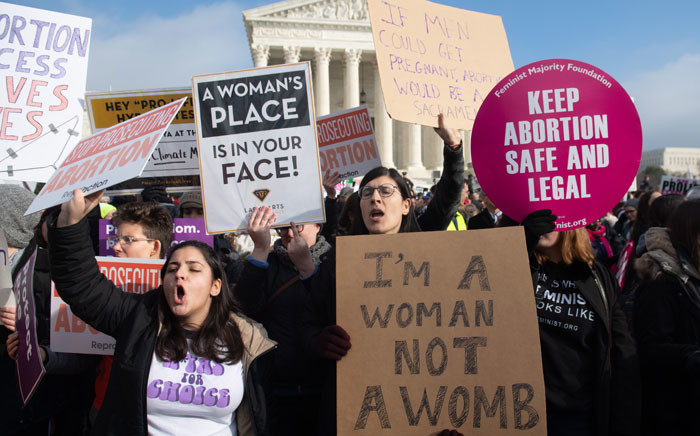 """FILE: Pro-choice activists hold signs in response to anti-abortion activists participating in the """"March for Life,"""" an annual event to mark the anniversary of the 1973 Supreme Court case Roe v. Wade, which legalised abortion in the US, outside the US Supreme Court in Washington, DC, 18 January 2019. Picture: AFP"""