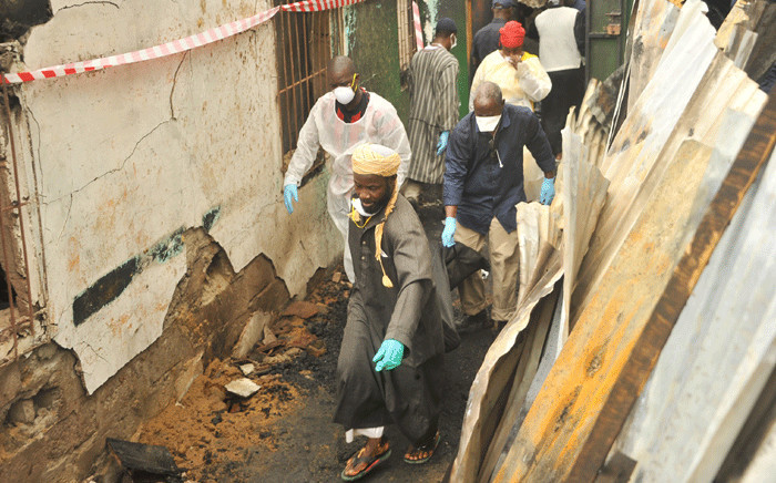 Rescuers hold a body after a fire at a Koranic school that killed at least 26 children and two teachers in Monrovia, Liberia, on September 18, 2019. Picture: AFP.