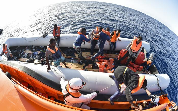 FILE: Men evacuate a rubber boat with the help of the crew of the Topaz Responder ship run by Maltese NGO Moas and the Italian Red Cross in the Mediterranean Sea. Picture: AFP.