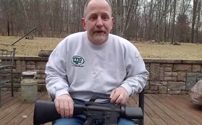 A screengrab of Scott Pappalardo holding a destroyed semi-automatic weapon.