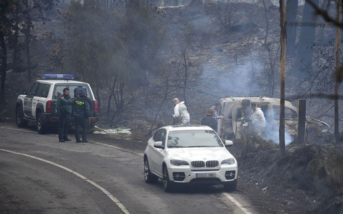 Policemen stand next a van where two people were trapped by flames of a fire in their vehicle in Chandebrito, near the town of Nigran, northwestern Spain, on 16 October 2017. Picture: AFP