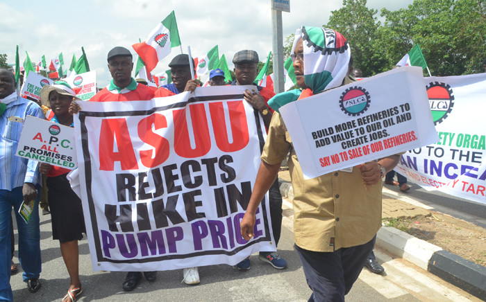 FILE: Workers and civil society groups carry placards as they march during a protest demanding that the government reinstate prices of fuel at 86.50 naira ($0.43, 0.38 euros) per litre in Lagos, on 18 May, 2016. Picture: AFP.