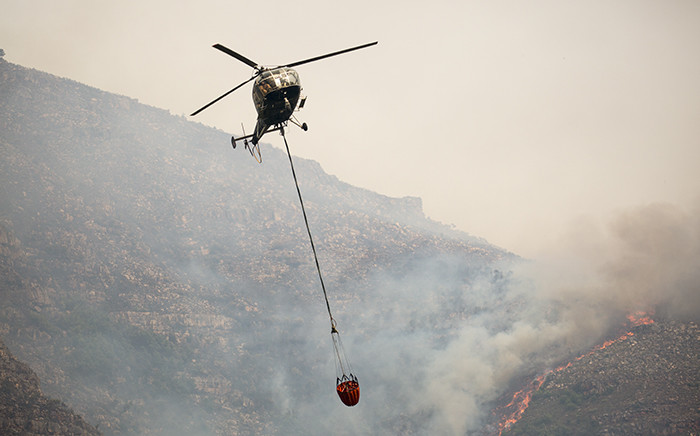 A helicopter water bombing the flames in the Jonkershoek valley on 11 March 2015. Picture: Aletta Gardner/EWN