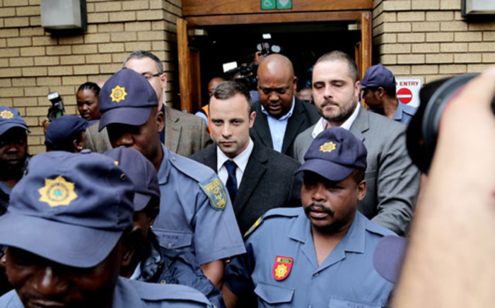 Oscar Pistorius leaves the Pretoria High Court under heavy security after the second day of his murder trial on 4 March 2014. Picture: Sebabatso Mosamo/EWN.