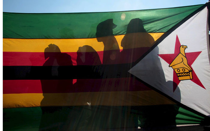 FILE: ZANU PF supporters wait behind the Zimbabwean national flag in Chitungwiza, Zimbabwe, 26 June 2008. Picture: EPA/STR