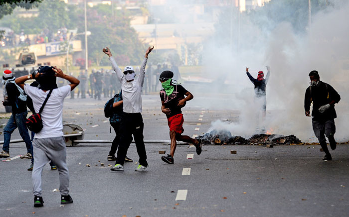FILE: Venezuelan opposition activists clash with riot police during a protest march against President Nicolas Maduro in Caracas. Picture AFP