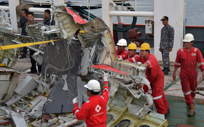 Indonesian crew of the Crest Onyx ship prepare to unload recovered wreckage of AirAsia flight QZ8501 at port in Kumai on January 11, 2015. Indonesian divers on 11 January found the crucial black box flight recorders of the AirAsia plane that crashed in the Java Sea a fortnight ago with 162 people aboard, the transport ministry said. Picture: AFP.