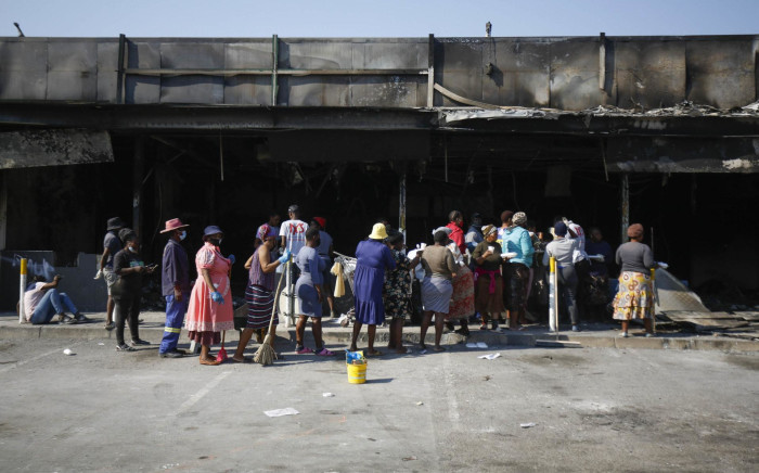 Volunteers cleaning up the gutted Dube Village Mall in Inanda, north of Durban, queue at what remains of the petrol station to have lunch on 20 July 2021.