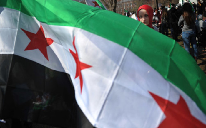 FILE: A woman behind a Syrian opposition flag during a rally against the Syrian government. Picture:  AFP.