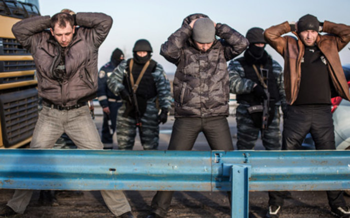 Men hold their hands up on their heads as they are searched by pro-Russian servicemen at Chongar checkpoint blocking the entrance to Crimea on 10 March 2014. Picture: AFP.