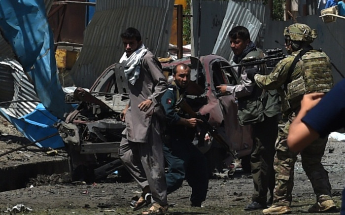 FILE: A Nato soldier points a weapon towards an Afghan man following a suicide car bomb attack that targeted foreign military vehicles in the Afghan capital Kabul on 30 June 2015. Picture: AFP.