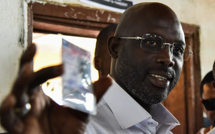 FILE: George Weah shows his voting card prior to casting his vote for Liberia's presidential and legislative elections at a polling station in Monrovia on 10 October 2017. Picture: AFP.