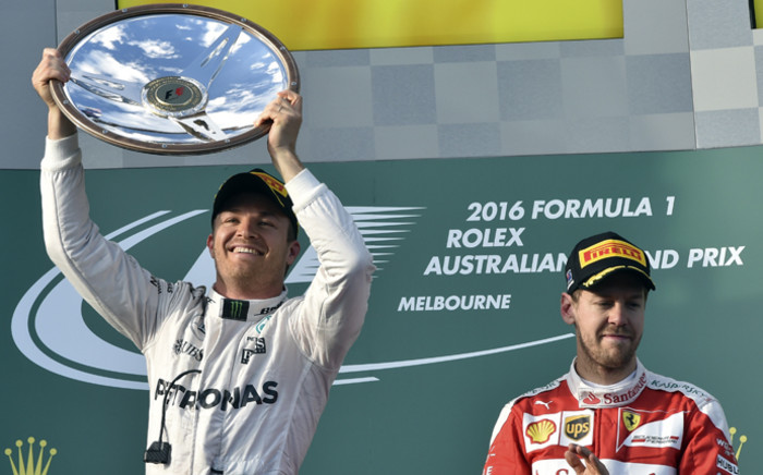 Mercedes AMG Petronas F1 Team's German driver Nico Rosberg celebrates his victory at the podium as Ferrari's German driver Sebastian Vettel applauds following the Formula One Australian Grand Prix in Melbourne on 20 March, 2016. Picture: AFP.
