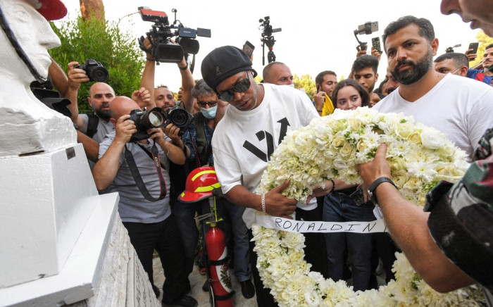 Brazil's former football star Ronaldinho (C) lays a wreath of flowers in remembrance of members of the Lebanese civil defence that were killed almost a year prior during the blast that rocked the port of Lebanon's capital Beirut, at the Beirut fire brigade headquarters near the port blast site on 29 July 2021. Picture: AFP