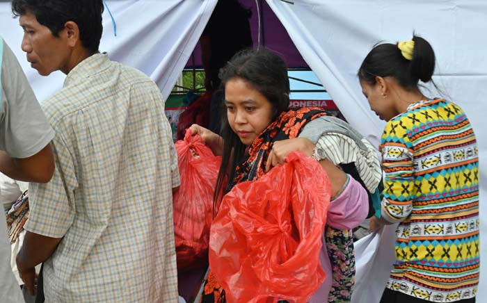 "A tsunami survivor collects donated clothing at a help centre in Citangkil village in Sumur, Pandeglang, Banten province on 25 December 2018, three days after a tsunami - caused by activity at a volcano known as the ""child"" of Krakatoa - hit the west coast of Indonesia's Java island. Picture: AFP"