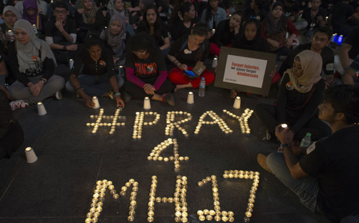 People gather during a candle-light vigil for the victims of the Malaysia Airlines flight MH17 from Amsterdam to Kuala Lumpur, at a shopping mall in Kuala Lumpur on July 18, 2014. Picture: AFP