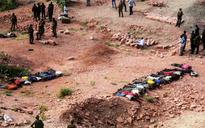 Kenyan soliders gather around the bodies of victims on the ground at a quarry near Mandera, northeastern Kenya on 2 December 2014. Picture: EPA.