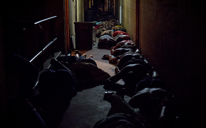 FILE. Men lie flat on the floor as police search their rooms for illegal weapons, stolen goods and drugs during an overnight Operation Fiela raid in Jeppestown. Picture: Thomas Holder/EWN.