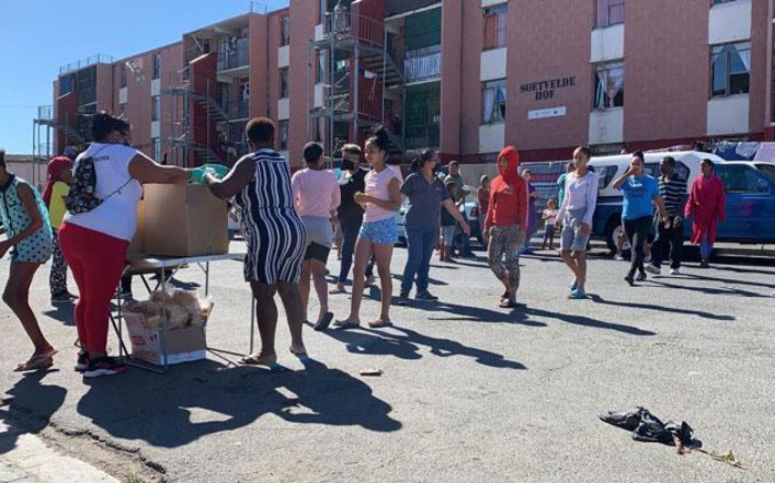 Clarkes Estate residents in Elsies River, Cape Town receive their meals from community activists on 22 April 2020. Picture: Kaylynn Palm/EWN
