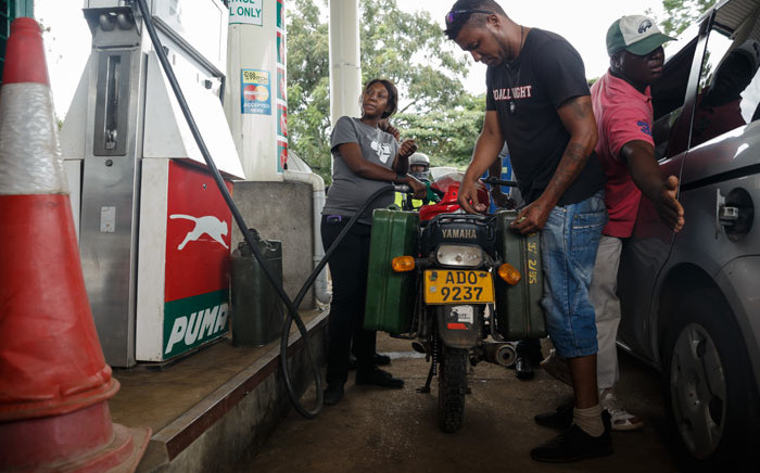 FILE: A petrol attendant serves a motorcyclist with two jerry cans attached to his motorbike at a fuel station, on 11 January 2019 in Harare, Zimbabwe. Motorists are spending nights waiting in long queues for petrol and diesel as the country is experiencing crippling fuel shortages. Picture: AFP