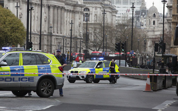 Armed police officers stand guard inside a security cordon, outside of the Houses of Parliament in central London on 22 March 2017 during an emergency incident. Picture: AFP