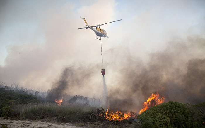 A helicopter water-bombs flames in Hawston, Elgin Valley, after fires have been raging there for two days. Picture: Thomas Holder/EWN.