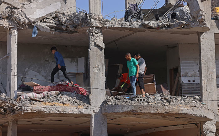Palestinians inspect a building, destroyed by Israeli strikes, in Beit Hanun in the northern Gaza Strip on 21 May 2021. A ceasefire in the conflict between Israel and Palestinian militants in the Gaza Strip, controlled by Islamist group Hamas, came into effect after 11 days of airstrikes and rocket fire. Picture: Emmanuel Dunand/AFP