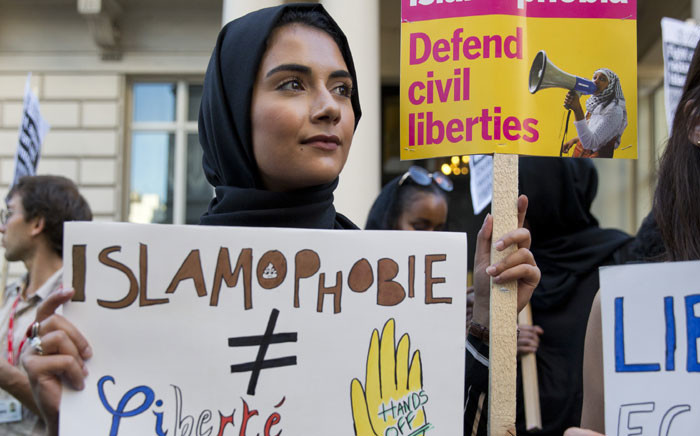 """FILE: A woman wearing a headscarf joins a demonstration organised by """"Stand up to Racism"""" outside the French Embassy in London on 26 August 2016. Picture: AFP."""