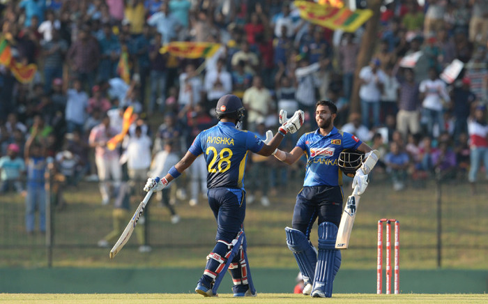 Sri Lanka's Kusal Mendis (R) is congratulated by teammate Avishka Fernando after he scored a century (100 runs) during the second one day international (ODI) cricket match between Sri Lanka and West Indies at the Suriyawewa Mahinda Rajapaksa International Cricket Stadium in the southern district of Hambantota on 26 February 2020. Picture: AFP.