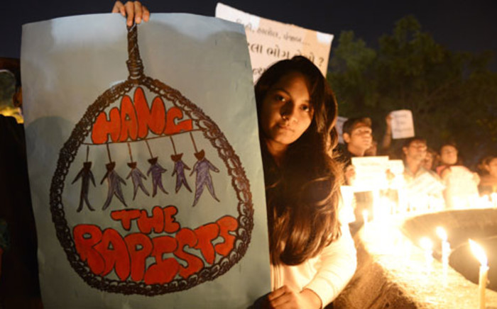 FILE: Indian protesters hold candles and posters during a rally in Ahmedabad on December 30, 2012, following following the cremation of a gangrape victim in the Indian capital.