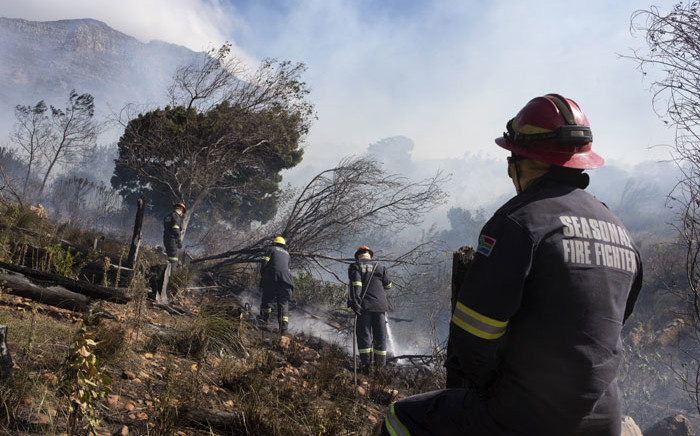 Firefighting teams dampen smouldering vegetation, finally getting a fierce forest fire under control on the foothills of Table Mountain in Cape Town on 19 April 2021. Picture: Rodger Bosch/AFP