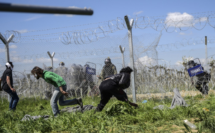 Refugees and migrants clash with Macedonian soldiers during a protest for the reopening of the border near their makeshift camp in the northern Greek border village of Idomeni, on 10 April, 2016. Picture: AFP.