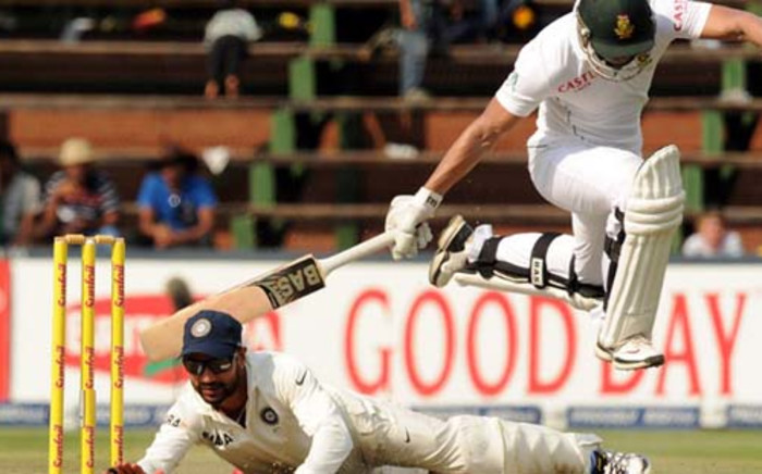 Indian fielder Shikhar Dhawan attempts to runout South African batsman Alviro Petersen on the fourth day of the first cricket Test between South Africa and India at the Wanderers Stadium in Johannesburg on December 21, 2013. Picture: AFP.