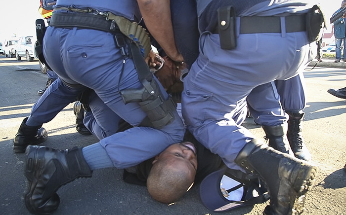 Police detain a taxi driver that resisted being taken in for questioning on 21 August in Thembalethu, George after drivers argued that a police road block, checking permits and roadworthiness was against their rights to do business. Picture: Thomas Holder/EWN.