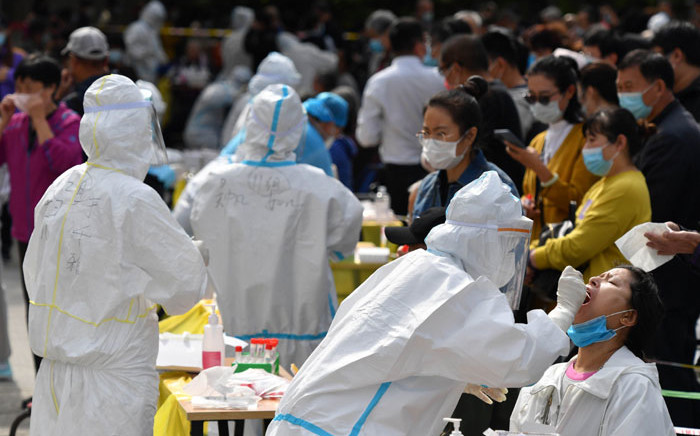 A health worker takes a swab from a resident to be tested for the COVID-19 coronavirus as part of a mass testing program following a new outbreak of the coronavirus in Qingdao, in China's eastern Shandong province on 13 October 2020. Picture: AFP