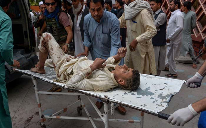 Volunteers carry an injured man on a stretcher to a hospital, following a bomb blast in Haska Mina district of Nangarhar Province on 18 October 2019. At least 62 people were killed by a blast inside an Afghan mosque during Friday prayers on 18 October, according to officials, a day after the United Nations said violence in the country had reached 'unacceptable' levels. Picture: AFP.