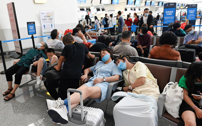Passengers rest as they wait for their flights at Beijing's Daxing International Airport on July 12, 2021, as hundreds of flights were cancelled in the capital due to torrential downpours and gale-force winds. Picture: Wang Zhao / AFP