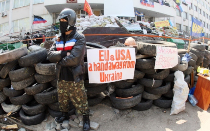 A pro-Russia activist guards a barricade outside the city government building seized by pro-Russia activists in the southeast city of Mariupol on 17 April. Picture: AFP.