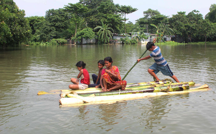 FILE: Indian residents use a makeshift raft to cross a flooded locality after the River Atreyee overflowed following heavy monsoon rains at Chakvrigu near Balurghat in South Dinajpur district of India's West Bengal state on 17 July 2019. Picture: AFP