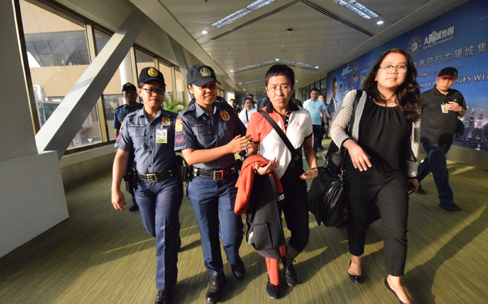 Philippine journalist Maria Ressa (2nd R), is escorted by police after an arrest warrant was served, shortly after arriving at the international airport in Manila on 29 March 2019. Ressa, a prominent critic of President Rodrigo Duterte, was arrested on a fraud charge, a colleague said on Ressa, a prominent critic of Duterte. Picture: AFP