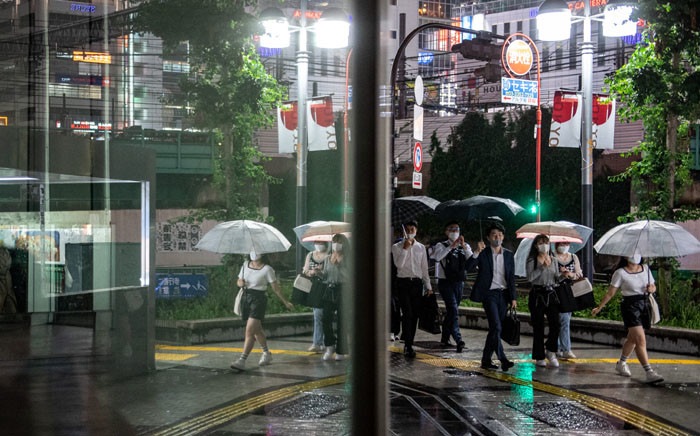 People walk on a street in Tokyo's Shinjuku district as Japan announces a new virus state of emergency stretching throughout the Tokyo Olympics, on 18 July 2021. Picture: Philip FONG/AFP