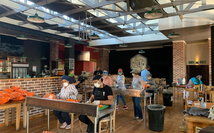 Vegetables simmer in giant copper vats at the Woodstock Brewery in Cape Town as workers and volunteers chop vegetables for soup. The pots were used to brew beer before alcohol sales were banned in the coronavirus lockdown. Picture: Facebook